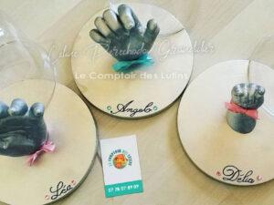 Empreintes mains enfants sur support rond avec cloche